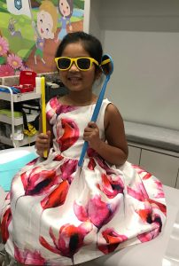 Child with giant toothbrush at Stonebrook Pediatric Dentistry